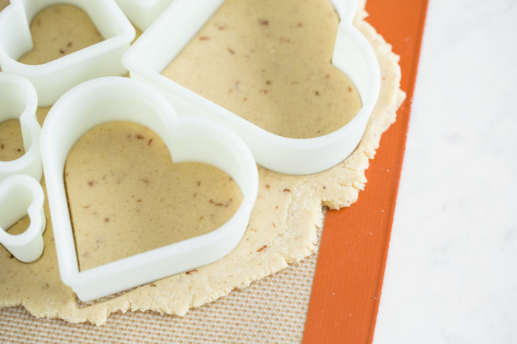 sugar cookies batter being cut with heart shapes