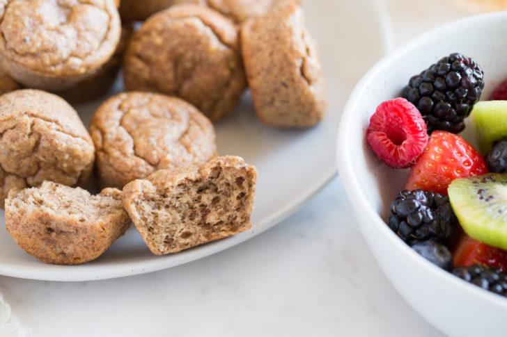 Breakfast muffins on white plate beside bowl of fresh fruit closeup