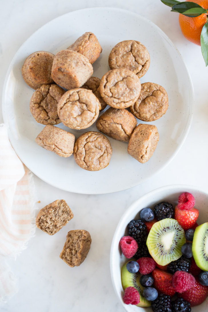 Breakfast Muffins on white plate with bowl of fresh fruit